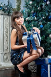 Attractive woman in blue glitter dress in interior. Christmas gift Stock Photography