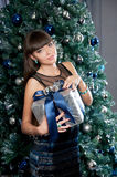 Attractive woman in blue glitter dress in interior. Christmas gift Stock Photo