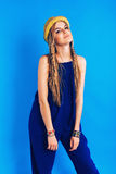 Attractive woman in blue jumpsuit and straw hat Stock Images