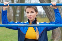 Attractive woman in  blue sport clothes is exercising outdoors stock images