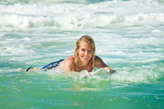 Attractive woman bodyboards on surfboard Royalty Free Stock Photo