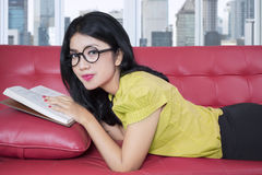 Attractive woman with book on the sofa Royalty Free Stock Photo