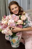 Attractive woman with bouquet of hundreds of flowers is spending time at home. Attractive young woman with bouquet of hundreds of flowers is spending time at stock image
