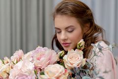 Attractive woman with bouquet of hundreds of flowers is spending time at home. Attractive young woman with bouquet of hundreds of flowers is spending time at royalty free stock images