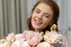 Attractive woman with bouquet of hundreds of flowers is spending time at home. Attractive young woman with bouquet of hundreds of flowers is spending time at royalty free stock image