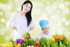 Attractive woman and boy make salad. Portrait of attractive young women and little boy make vegetables salad, shot with bokeh background Royalty Free Stock Image