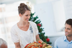 Attractive woman bringing a roast chicken at table Stock Image