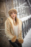 Attractive woman with brown fur cap and jacket enjoying the winter. Side view of fashionable blonde girl posing against bridge Stock Image