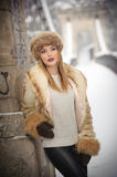 Attractive woman with brown fur cap and jacket enjoying the winter. Side view of fashionable blonde girl posing against bridge Royalty Free Stock Image