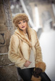 Attractive woman with brown fur cap and jacket enjoying the winter. Side view of fashionable blonde girl posing against bridge Royalty Free Stock Photography