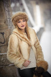 Attractive woman with brown fur cap and jacket enjoying the winter. Side view of fashionable blonde girl posing against bridge Royalty Free Stock Photo