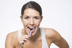 Attractive woman brushing her teeth Royalty Free Stock Images