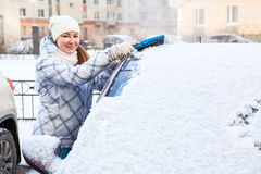 Attractive woman brushing snow from the car windshield Stock Photos