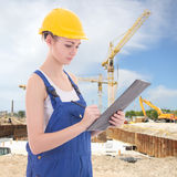 Attractive woman builder writing something in clipboard Royalty Free Stock Photos