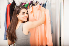 Attractive woman buying some clothes. Beautiful young woman looking at a blouse while doing some shopping at a clothing store and smiling stock photo