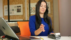 Attractive woman buying their own pay cards in the office using the terminal. She holds and pulls out a card payment stock footage