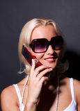Attractive woman calling by mobile and smiling. Attractive happy blond woman calling by mobile and smiling Stock Photography