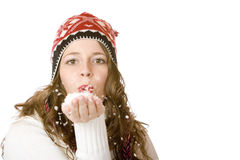 Attractive woman with cap blows snow from palm Stock Image