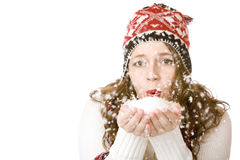 Attractive woman with cap and scarf blowing snow Stock Photos