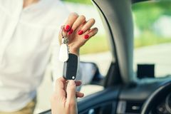 An attractive woman in a car gets the car keys. Rent or purchase of auto. An attractive woman in a car gets the car keys. Rent or purchase of auto - concept stock photo
