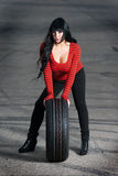 Attractive woman with car tire Stock Photography