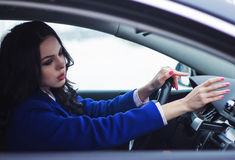 Attractive woman in the car warms her hands Stock Images