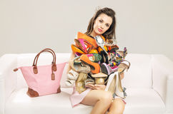 Attractive woman carrying a heap of shoes Stock Image