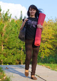 Attractive woman carrying a mat Royalty Free Stock Photography