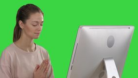 Attractive woman in a chair at the table with computer meditating on a Green Screen, Chroma Key. Close up. Attractive woman in a chair at the table with stock video