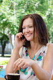 Attractive woman chatting on a mobile. Phone in her garden while stirringa cup of delicious coffee Stock Photos