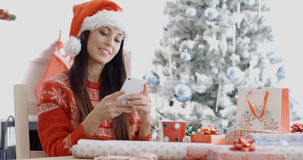 Attractive woman checking for Christmas messages. Attractive festive young woman in a Santa hat sitting in front of the Xmas tree checking for Christmas messages Stock Photo