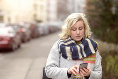 Attractive woman checking her mobile in a street Royalty Free Stock Photography