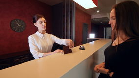 Attractive woman checking in hotel reception lobby. Travelling on vacation carrying luggage. 4K stock footage