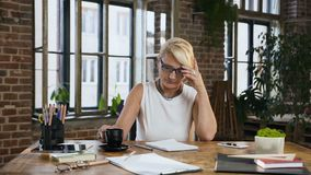 Attractive woman is checking reporting in the diary while drinks coffee sitting behind the desk in home office .Indoors. Business, education and people concept stock footage