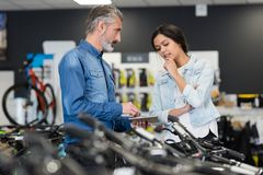 Attractive woman chooses bike in sport store royalty free stock photo