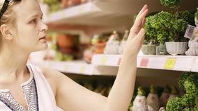 Attractive woman choosing potted plants stock footage