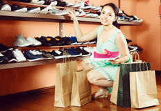 Attractive woman is choosing sport shoes for jogging Royalty Free Stock Images