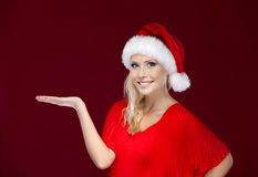Attractive woman in Christmas cap gestures palm up Royalty Free Stock Photography
