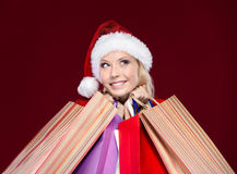 Attractive woman in Christmas cap hands packets Stock Photography