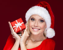 Attractive woman in Christmas cap hands a present Royalty Free Stock Image