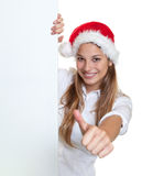 Attractive woman with christmas hat showing thumb behind a signboard Stock Images
