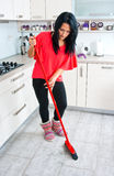 Attractive woman cleaning broken glass in kitchen Royalty Free Stock Photo