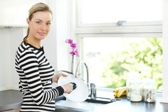 Attractive woman cleaning dishes. Attractive blonde woman standing at the kitchen sink cleaning dishes as part of her daily household chores and routine Stock Photo