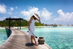 Attractive woman cleans sand off her feets on a wooden jetty Stock Photo