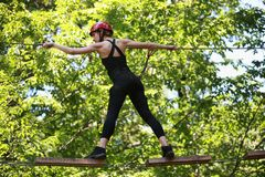 Attractive woman climbing in adventure rope park in safety equipment. Back view Royalty Free Stock Image