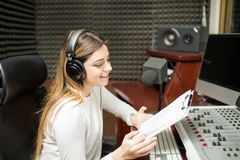 Female presenter hosting a radio talk show. Attractive woman with clipboard in hand sitting in soundproof room at radio station and hosting a talk show live Royalty Free Stock Photo