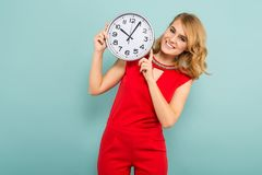 Attractive woman with clocks. Portrait of attractive blonde woman in red isolated on blue background holding clocks time limit punctuality concept Stock Photo