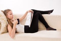 Attractive woman with a coffee cup lying on a sofa Stock Images