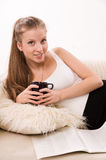 Attractive woman with a coffee cup lying on a sofa Royalty Free Stock Photos