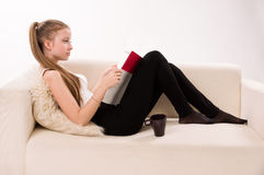 Attractive woman with a coffee cup lying on a sofa Stock Photos